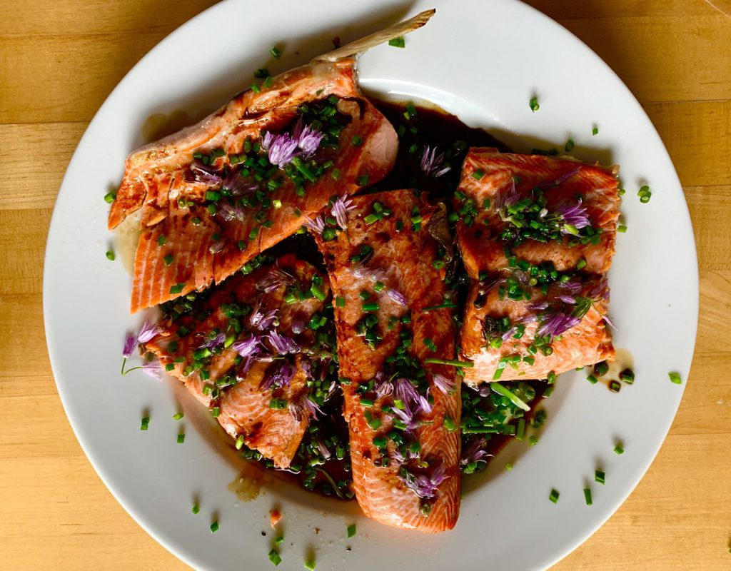 salmon on a plate sprinkled with purple flowers
