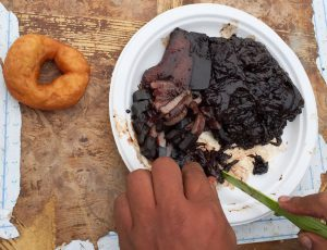 a donut sitting next to a place of black fermented whale