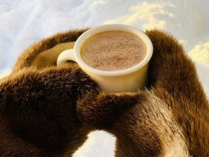 Cup of coffee in fur-mitten-covered hands
