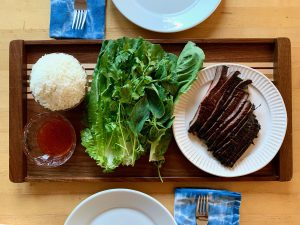 steak, lettuce, sauce and rice on a tray
