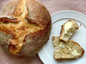 Loaf of bread and a slice of bread with butter