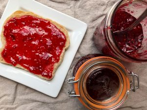 Toast spread with red jam and a jam jar